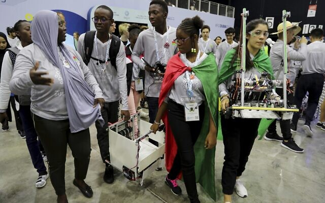 In this Friday, Oct. 25, 2019 photo, different team members carry their robots during the First Global Challenge, a robotics and artificial intelligence competition in Dubai, United Arab Emirates.  (AP Photo/Kamran Jebreili)