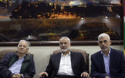 Yahya Sinwar, right, the Hamas terror group's leader in the Gaza Strip, sits with Hamas chief Ismail Haniyeh, center, as they meet the Head of the Central Elections Commission, Hanna Nasser,  in Gaza City, October 28, 2019. (AP Photo/Khalil Hamra)