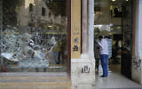 A client enters a bank with a front window shattered during anti-government protests in Beirut, Lebanon, Nov. 1, 2019. (AP Photo/Hussein Malla)
