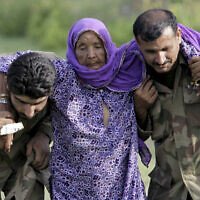 In this July 30, 2010 file photo, Pakistani army soldiers help an elderly villager evacuated from a flooded area in Nowshera, Pakistan. As Turkish forces invaded northern Syria in early October 2019, supporters of the offensive launched an online misinformation campaign. Dozens of misleading images claiming to show Turkey's soldiers cuddling babies, feeding hungry toddlers and carrying elderly women, including this image from 2010, spread across Twitter and Instagram where they were liked, retweeted and viewed thousands of times. (AP Photo/Mohammad Sajjad, File)