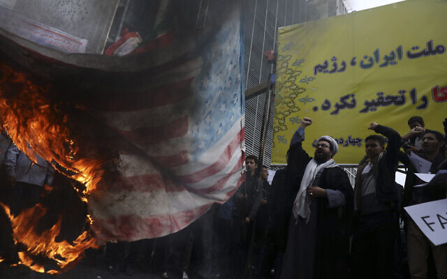 Iranian demonstrators chant slogans as they set fire to a makeshift US flag during an annual rally in front of the former US Embassy in Tehran, Iran, Nov. 4, 2019 (AP Photo/Vahid Salemi)