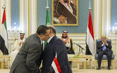 In this photo released by the Saudi Royal Palace, Yemeni Southern Transitional Council member and former Aden Governor Nasser al-Khabji, left, and Yemen's deputy Prime Minister Salem al-Khanbashi greet each other before signing a power-sharing deal witnessed by Yemen's president, Abed Rabbo Mansour Hadi, background right, Saudi Arabia's Crown Prince Mohammed bin Salman, center, and Abu Dhabi's Crown Prince, Mohammed bin Zayed Al Nahyan, in Riyadh, Saudi Arabia, November 5, 2019. (Bandar Aljaloud/Saudi Royal Palace via AP)