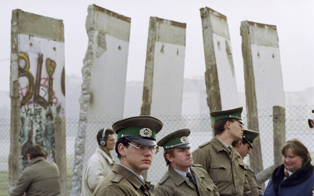 In this Nov. 13, 1989, file photo, East German border guards stand in front of segments of the Berlin Wall, which were removed to open the wall at Potsdamer Platz passage in Berlin (AP Photo/John Gaps III, File)