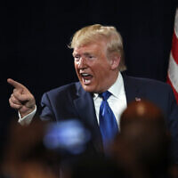 US President Donald Trump gestures to an audience member after speaking at his Black Voices for Trump rally, Nov. 8, 2019, in Atlanta. (AP Photo/John Bazemore)
