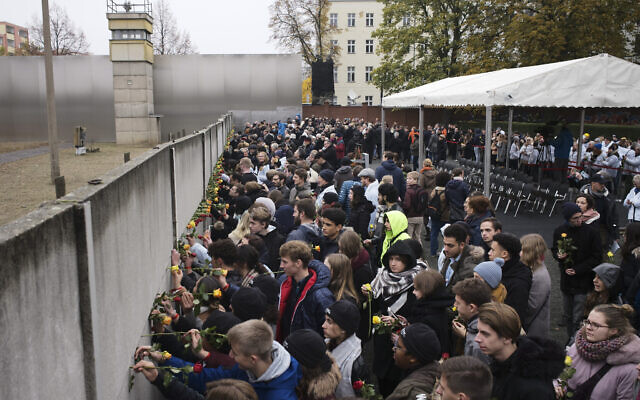 Young people stuck flowers in remains of the Berlin Wall during a commemoration ceremony to celebrate the 30th anniversary of the fall of the Berlin Wall at the Wall memorial site at Bernauer Strasse in Berlin,  Nov. 9, 2019. (AP Photo/Markus Schreiber)