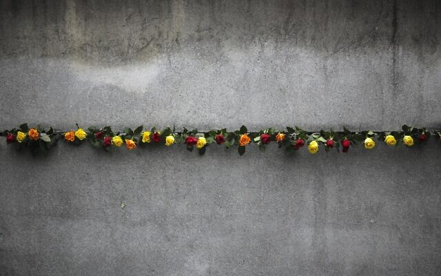 Flowers stuck in remains of the Berlin Wall during a commemoration ceremony to celebrate the 30th anniversary of the fall of the Berlin Wall at the Wall memorial side at Bernauer Strasse in Berlin, Nov. 9, 2019. (AP Photo/Markus Schreiber)