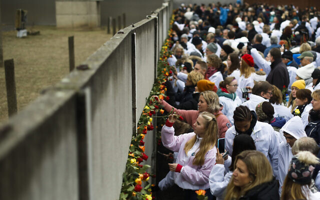 People stuck flowers in remains of the Berlin Wall during a commemoration ceremony to celebrate the 30th anniversary of the fall of the Berlin Wall at the Wall memorial site at Bernauer Strasse in Berlin, Nov. 9, 2019. (AP Photo/Markus Schreiber)