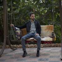 Palestinian Karam Qawasmi, who was shot in the back by Israeli forces in an incident caught on video last year, sits in his garden, in the West Bank city of Hebron, Sunday, Nov. 10, 2019. (AP Photo/Majdi Mohammed)