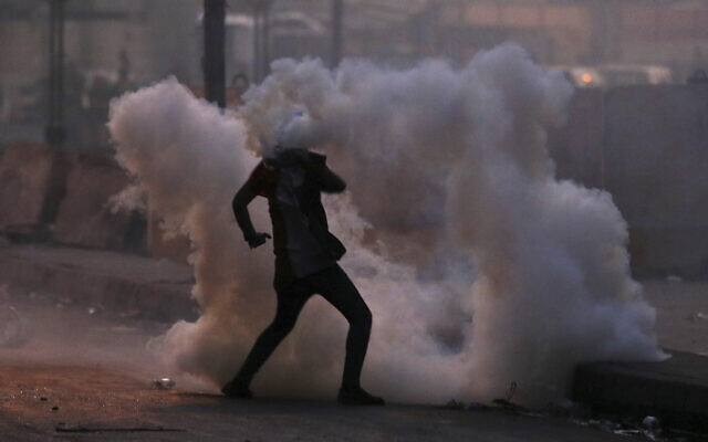 An anti-government protester is surrounded by tear gas fired by Iraqi security forces in an effort to disperse demonstrators, in central Baghdad, Iraq, November 10, 2019. (Hadi Mizban/AP)