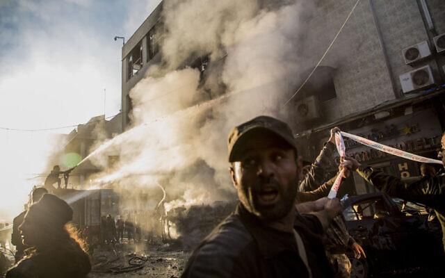 Firemen spray water after a car bomb blast in the Syrian city of Qamishli on Monday, November 11, 2019. (AP Photo/Baderkhan Ahmad)