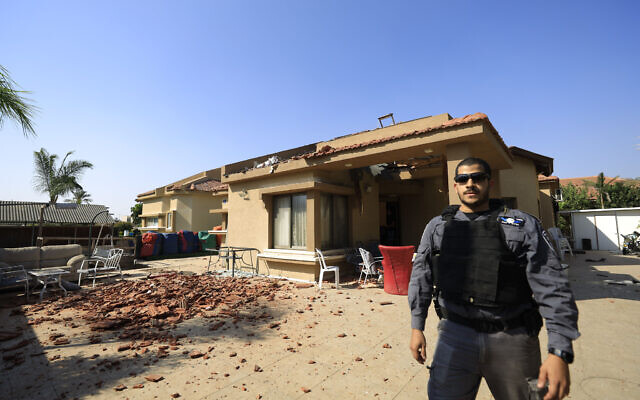 A policeman stands in front of a house hit by a rocket fired from Gaza Strip that landed in Netivot, Israel, November 12, 2019. (Tsafrir Abayov/AP)