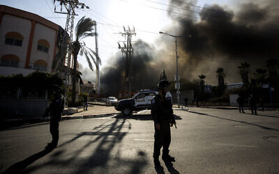 Illustrative: Police stand guard after a factory was hit by a rocket fired from the Gaza Strip, in Sderot, southern Israel November 12, 2019. (AP Photo/Tsafrir Abayov)