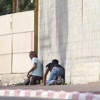 People take cover during an air-raid warning siren in Sderot, southern Israel on November 13, 2019. (AP/Ariel Schalit)