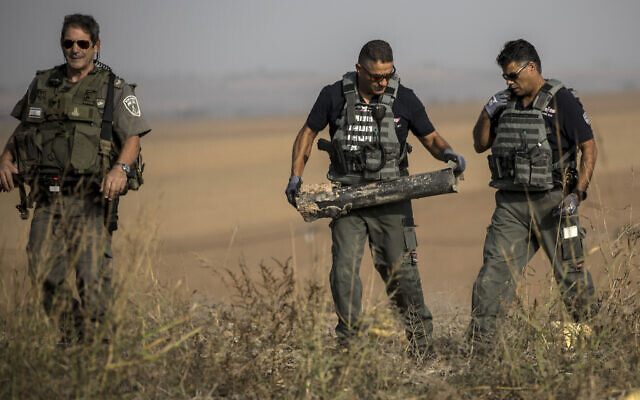 Israeli police sappers remove a rocket fired from the Gaza Strip in farmland near the Israel-Gaza border, November 13, 2019. (AP Photo/Tsafrir Abayov)