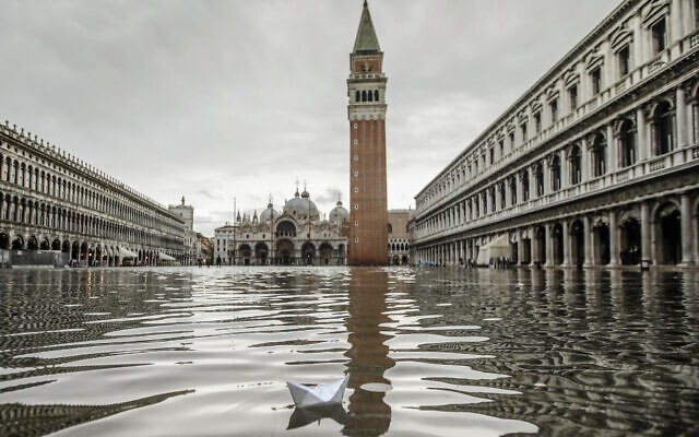 A paper boat floats in a flooded St. Mark's Square in Venice, November 15, 2019 (AP Photo/Luca Bruno)