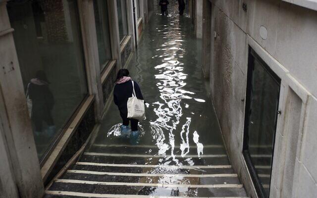 People wade their way through water in Venice, Italy, November 15, 2019 (AP Photo/Luca Bruno)