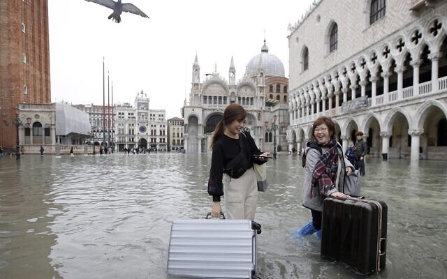 Tourists push their luggage in a flooded St. Mark's Square, in Venice, Nov. 13, 2019. (AP Photo/Luca Bruno)