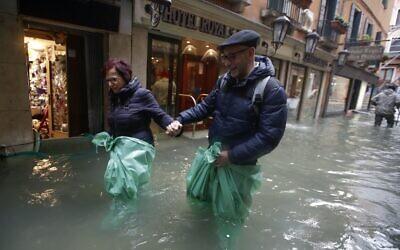 A couple wades their way through water in Venice, Italy, Nov. 15, 2019. (AP Photo/Luca Bruno)