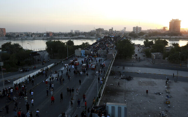 Protesters take control of some concrete walls and barriers erected by security forces to close the Sinak bridge leading to the Green Zone government areas, during clashes between Iraqi security forces and anti-government demonstrators in Baghdad, Iraq, Saturday, Nov. 16, 2019. (AP Photo/Hadi Mizban)