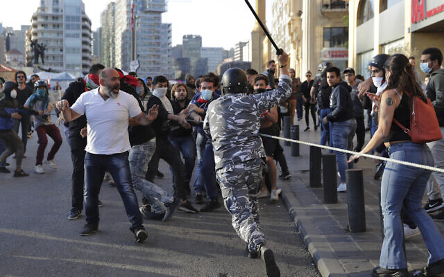 A police officer raises his baton to anti-government protesters during clashes in downtown Beirut, Lebanon, Nov. 19, 2019. (Hassan Ammar/AP)