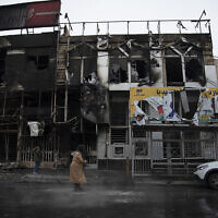 People walk past buildings which were burned during protests in the city of Karaj, west of the capital Tehran that followed a nation-wide raise in gasoline prices in, Iran, seen on November 18, 2019. (Masoume Aliakbar/ISNA via AP)
