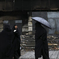 Women walk past a building damaged during recent protests, in Shahriar, Iran, some 40 kilometers (25 miles) southwest of the capital, Tehran, November 20, 2019. (AP Photo/Vahid Salemi)