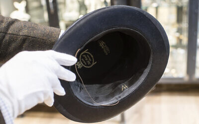 A man holds a hat with the initials of Adolf Hitler prior to an auction in Grasbrunn, Germany on Wednesday, November 20, 2019.  (Matthias Balk/dpa via AP)