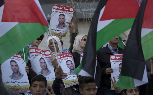 Protesters fly Palestinian flags and carry posters with pictures of Palestinian prisoner in Israeli jail, Sami Abu Diak, who died of cancer, during a protest in the West Bank city of Ramallah, November 26. 2019. (AP Photo/Nasser Nasser)