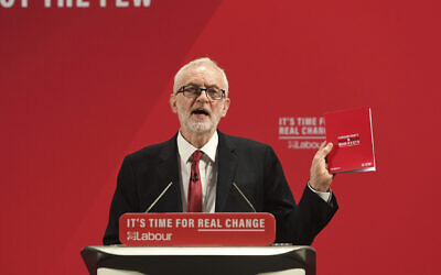 Britain's main opposition Labour Party leader Jeremy Corbyn holds a copy of the party race and faith manifesto, in London, November 26, 2019. (Joe Giddens/PA via AP)