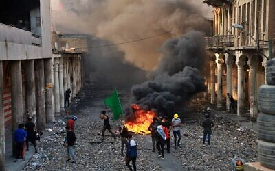Anti-government protesters set fire while security forces close Rasheed Street during clashes in Baghdad, Iraq, Nov. 28, 2019  (AP Photo/Khalid Mohammed)