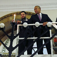 From left, Rabbi Rachmiel Liberman, then Massachusetts Governor Deval Patrick and Massachusetts House Speaker Robert DeLeo light candles on an 18-foot menorah to mark the arrival of Hanukkah during a ceremony at the Statehouse in Boston, December 16, 2014. (AP Photo/Elise Amendola)