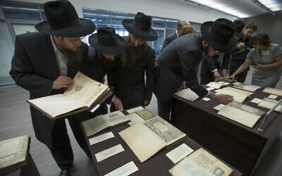 Visitors look through books before Russian President Vladimir Putin's visit to  the library of the Schneerson family of Hasidic rabbis in the Jewish Museum in Moscow, June 13, 2013.  (AP Photo/Alexander Zemlianichenko)