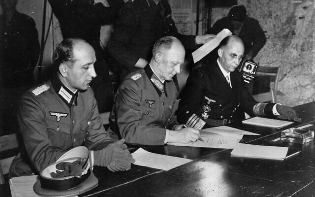 In this May 7, 1945 file photo, Gen. Alfred Jodl, center, signs the unconditional surrender of all armed German forces imposed by the Allied Powers, at Supreme Commander Eisenhowers headquarters in Rheims, France. He is flanked by Gen. Wilhelm Oxenius, Commander of the German Luftwaffe, left, and General Admiral and Commander in Chief of the German fleet, Hans-Georg von Friedeburg, right. (AP Photo/File)