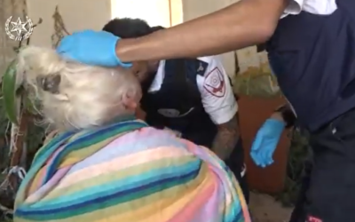 A woman in the southern city of Ashkelon injured by a rocket fired from the Gaza Strip is treated by paramedics on November 13, 2019. (Screen capture: Twitter)