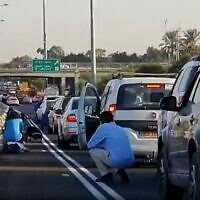 Screen capture from video of Israeli motorists crouching beside their vehicles on a major highway as sirens blare warning of incoming rocket fire from the Gaza Strip, November 12, 2019. (Twitter)