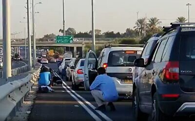 Illustrative: Screen capture from video of Israeli motorists crouching beside their vehicles on a major highway as sirens blare warning of incoming rocket fire from the Gaza Strip, November 12, 2019. (Twitter)
