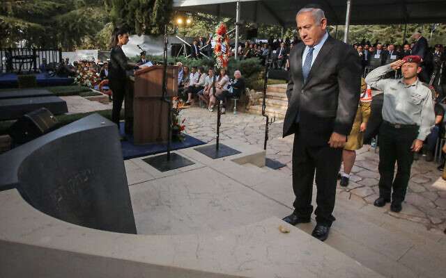 Prime Minister Benjamin Netanyahu stands infront of the tombstone of Late Prime Minister Yitzhak Rabin's during a memorial service marking 23 years since the assasination, held at Mount Herzl cemetery in Jerusalem on October 21, 2018. (Marc Israel Sellem/POOL )