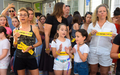Illustrative: Israeli school kids, Filipino workers, and their children take part at a protest against deportation of children's of Filipino workers on the first day of school, outside the Balfour School in Tel Aviv, on September 1, 2019. (Avshalom Shoshoni/Flash90)