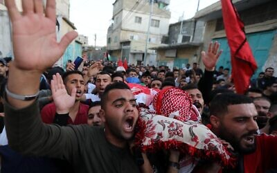 Mourners carry the body of 22-year-old Palestinian man Omar Haithm al-badawi who was shot dead by Israeli forces during clashes in al-arowb camp in the West Bank city of Hebron, on November 11, 2019. (Wisam Hashlamoun/Flash90)