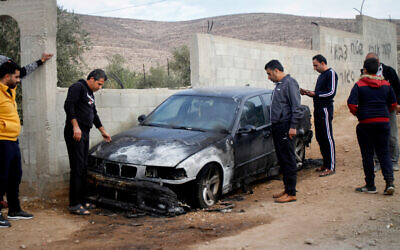 Palestinian men inspect a car that was burnt in a suspected hate crime in the northern West Bank village of Beit Dajan on November 22, 2019. (Nasser Ishtayeh/Flash90)