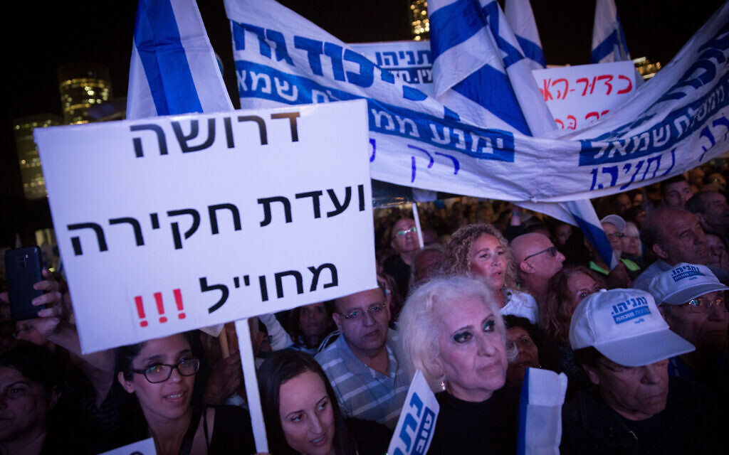 A supporter of Prime Minister Benjamin Netanyahu holds up sign saying 'We demand an overseas commission of inquiry' during a rally in Tel Aviv on November 26, 2019. Miriam Alster/Flash90)