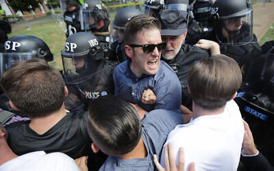 """White supremacist Richard Spencer, center, and supporters clash with police after the """"Unite the Right"""" rally in Charlottesville, Virginia, was declared unlawful, August 12, 2017. (Chip Somodevilla/Getty Images/via JTA)"""