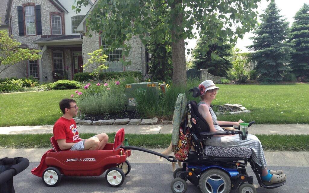 Jenni Kleinman Berebitsky pulls her husband Jeff with her motorized wheelchair. (From the film 'Grateful')