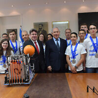 Prime Minister Benjamin Netanyahu (center right) and Science Minister Ofir Akunis greet the Israeli teen delegation upon their return from the unofficial 'Robotics Olympics' in Dubai. (Kobi Gideon/GPO)