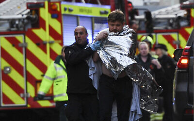 Police assist an injured man near London Bridge in London, on November 29, 2019 after a terror stabbing in the area. (Daniel Sorabji/AFP)
