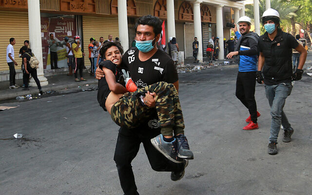 An injured protester is rushed to a hospital during clashes between Iraqi security forces and anti-government protesters in central Baghdad, Iraq, November 7, 2019. (AP Photo/Hadi Mizban)
