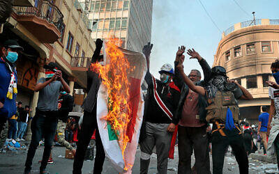 Iraqi anti-government protesters burn an Iranian flag during protests in Baghdad, Iraq, November 29, 2019. (AP Photo/Hadi Mizban)