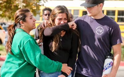 A student is comforted at a park following a shooting at Saugus High School that killed two, November 14, 2019, in Santa Clarita, California. (AP Photo/Ringo H.W. Chiu)