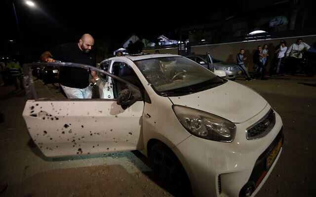 A man checks a car damaged by shrapnel from a missile fired from Gaza into Sderot, Israel, November 1, 2019. (AP Photo/Tsafrir Abayov)