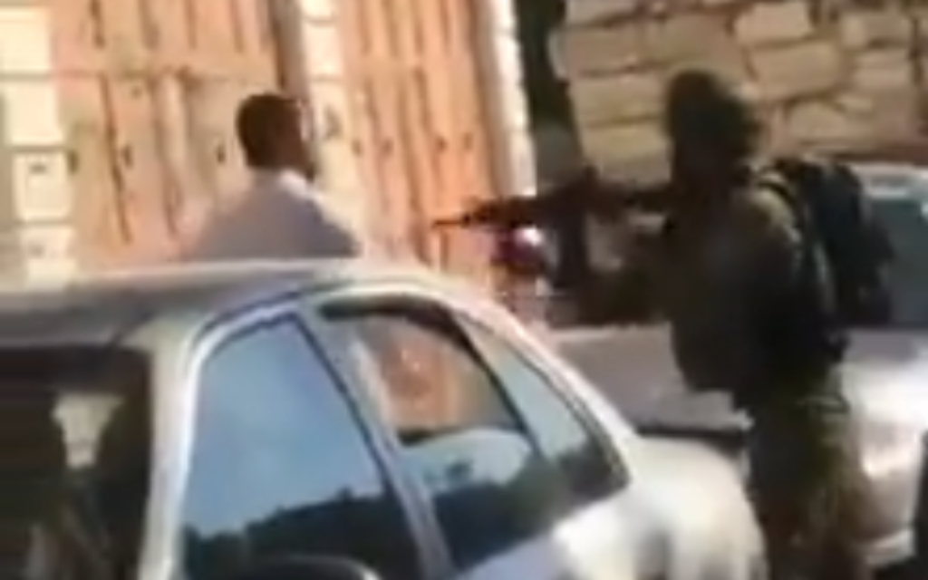 IDF troops filmed shoving, aiming gun at Palestinian father in front of child